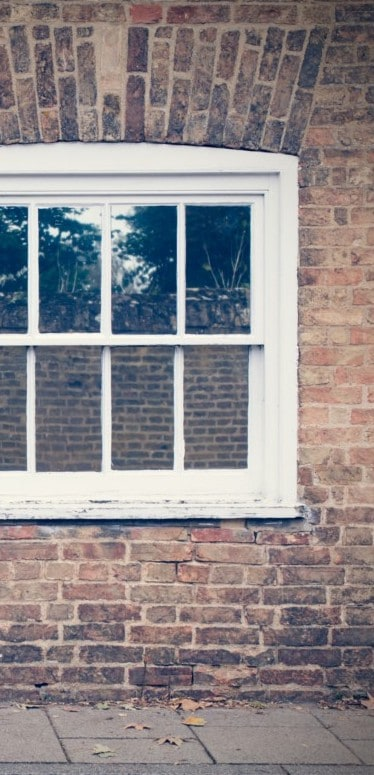white wooden window and brick wall