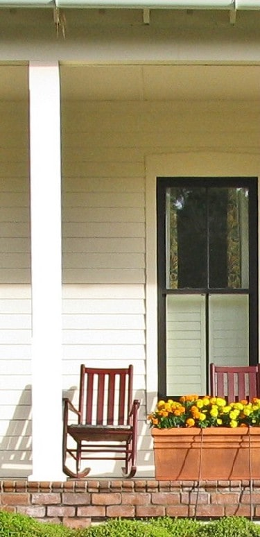 porch of wood sided house, rocking chair on porch