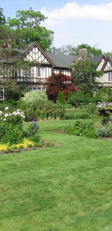 lawn and garden with flowers, large heritage buillding in background